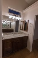 Vanity in master bathroom with window over the mirror