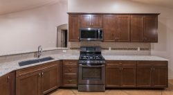 Kitchen cabinets with sink, stainless stove, and microwave hood fan.