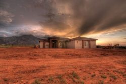 evening lighting rays from behind new custom home in Hereford, AZ