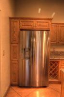 Stainless steel fridge wrapped with custom built cabinetry